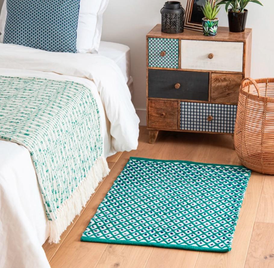 Alfombra de algodón color crudo con motivos decorativos gráficos verdes y azules 60x90