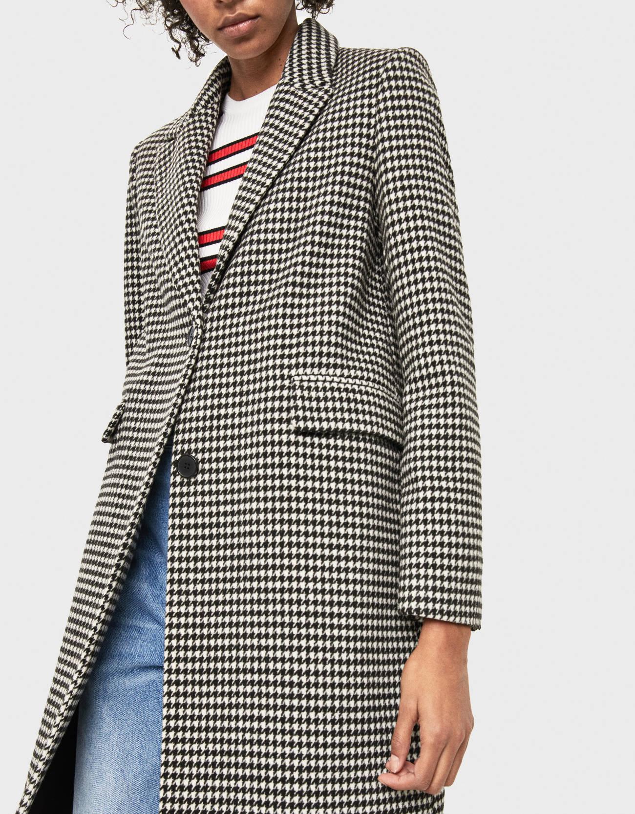 Abrigo largo de lana con cuello solapa y bolsillos en frontal. Cierre mediante botones.