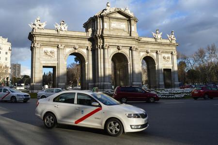 Un taxi pasando por la Puerta de Alcalá de Madrid