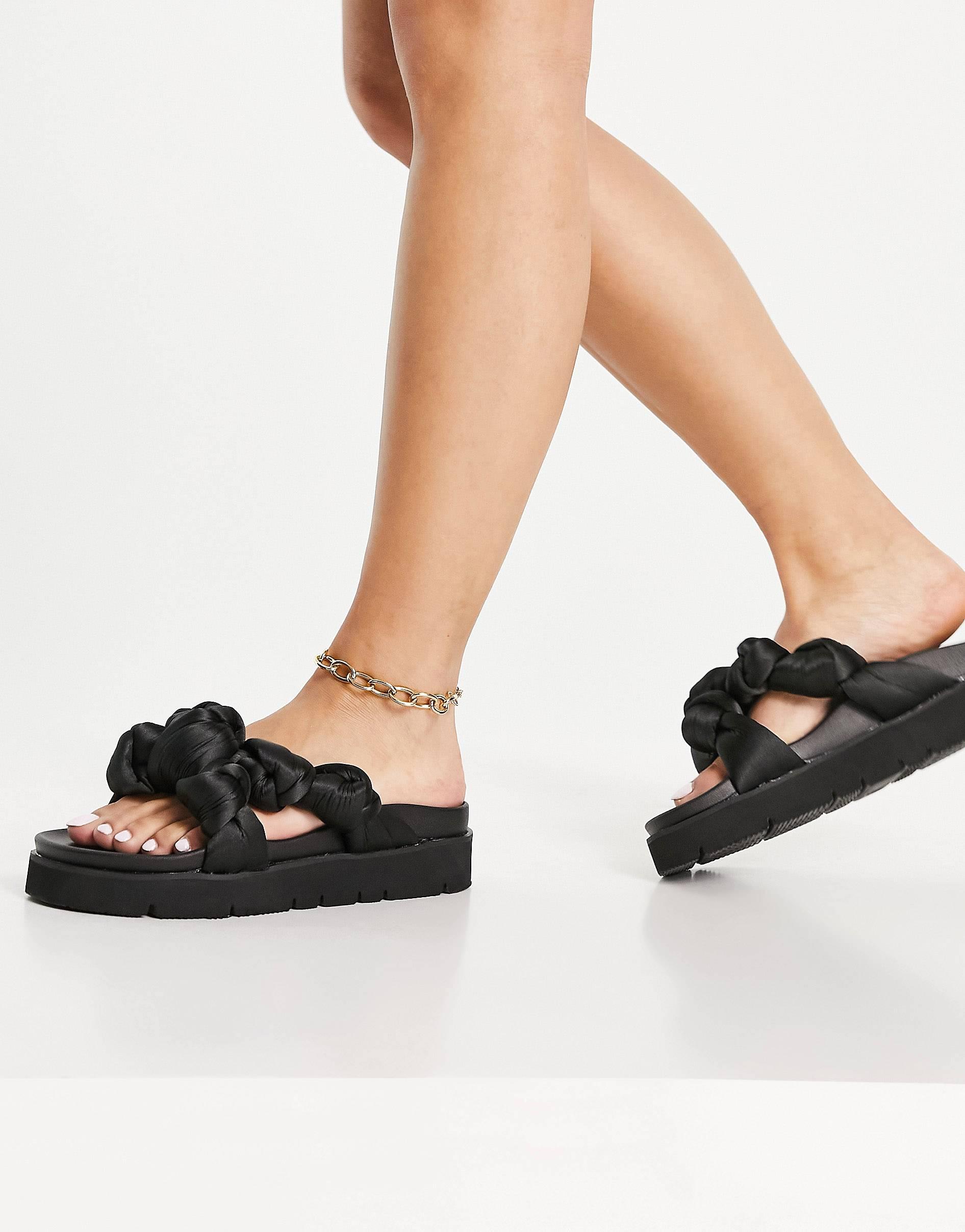 Sandalias negras con plataforma plana y diseño trenzado.
