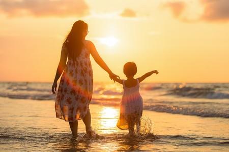 Madre e hija en la orilla al atardecer