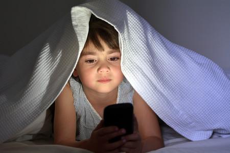 Niño mirando el móvil a oscuras