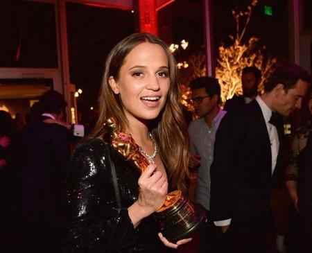 Alicia Vikander en una fiesta tras ganar el Oscar (Michael Fassbender detrás)