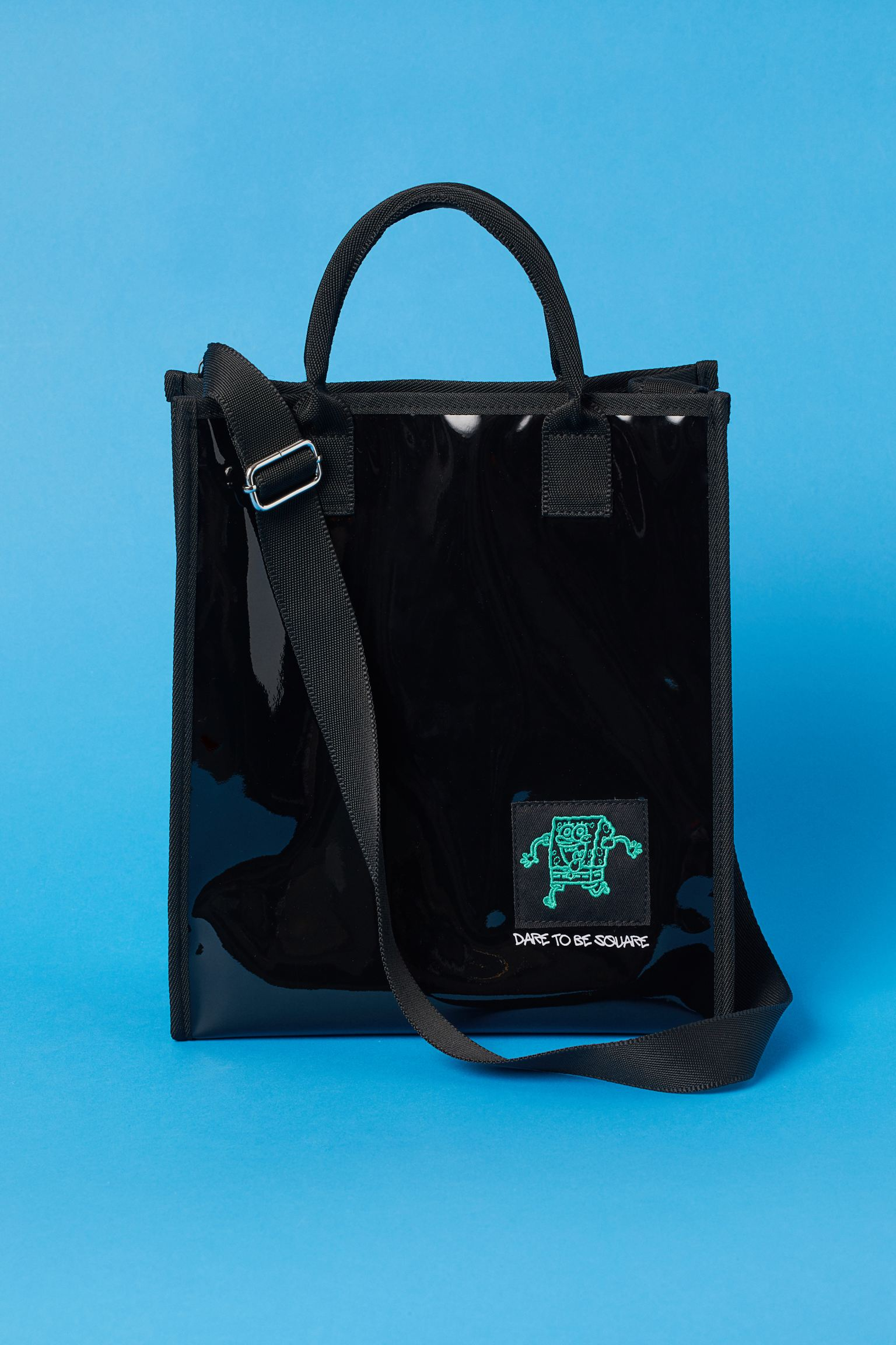 Bolsa shopper en plástico de charol con ribetes y asas revestidos de tela, aplicación delante y correa ancha. Alto 30 cm. Largo 26 cm. Ancho 11 cm.