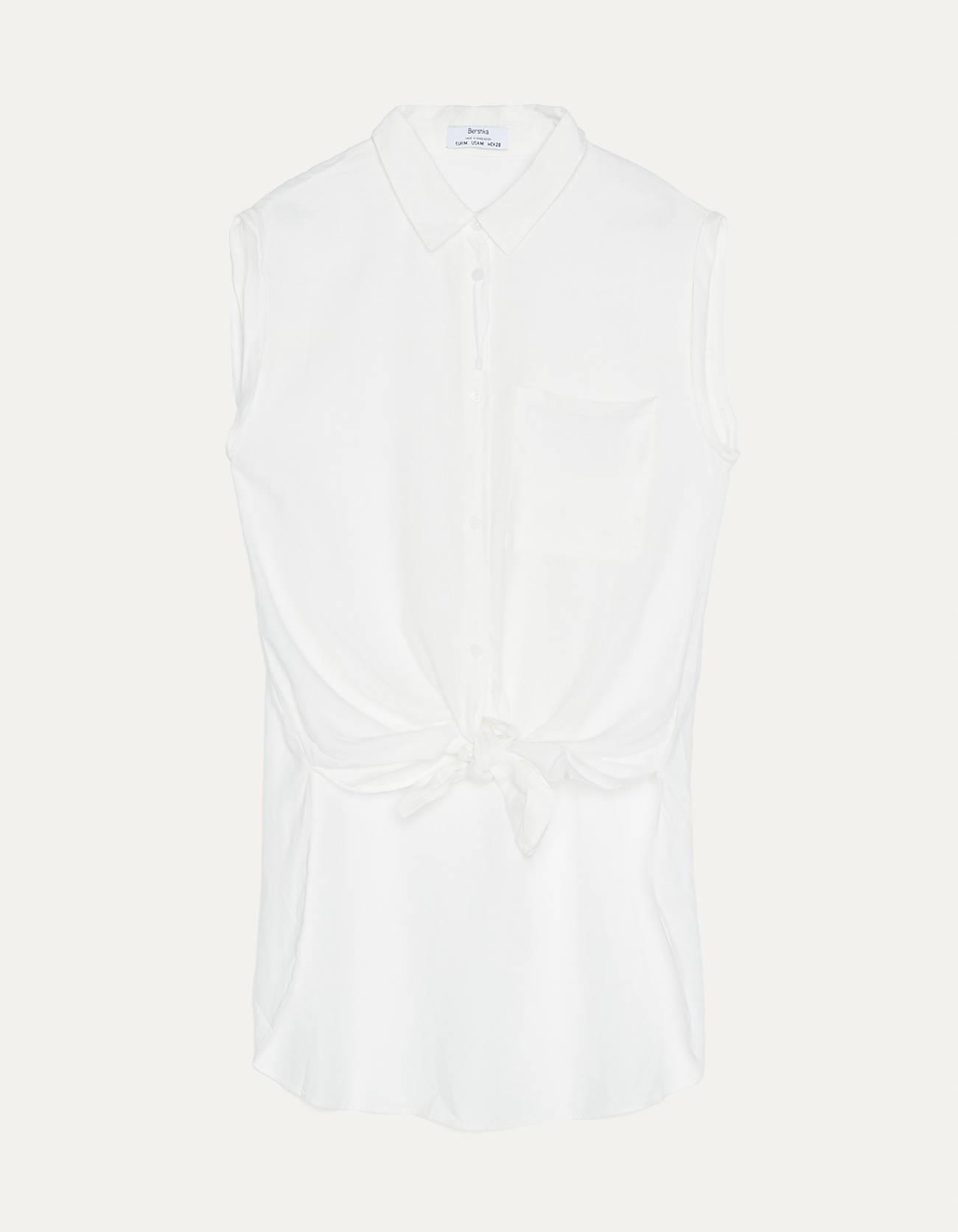 Camisa blanca sin mangas con nudo delantero.