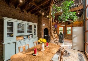 Una cocina de estilo rústico contemporáneo con un árbol central como protagonista