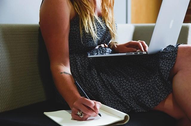 Mujer escribe en una libreta con un portátil sobre las piernas.