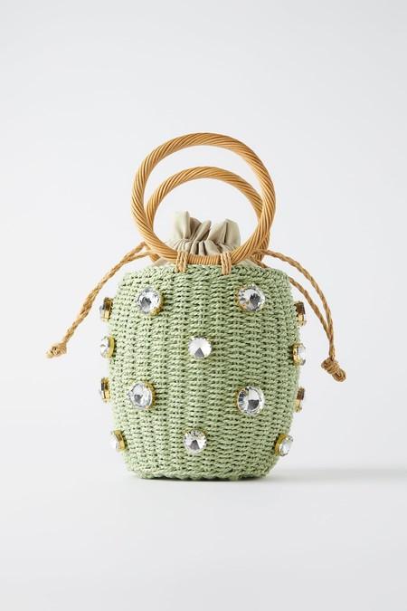 Bolso formato cesta de color verde. Cuerpo trenzado con detalle de joyas. Asas de mano circulares.