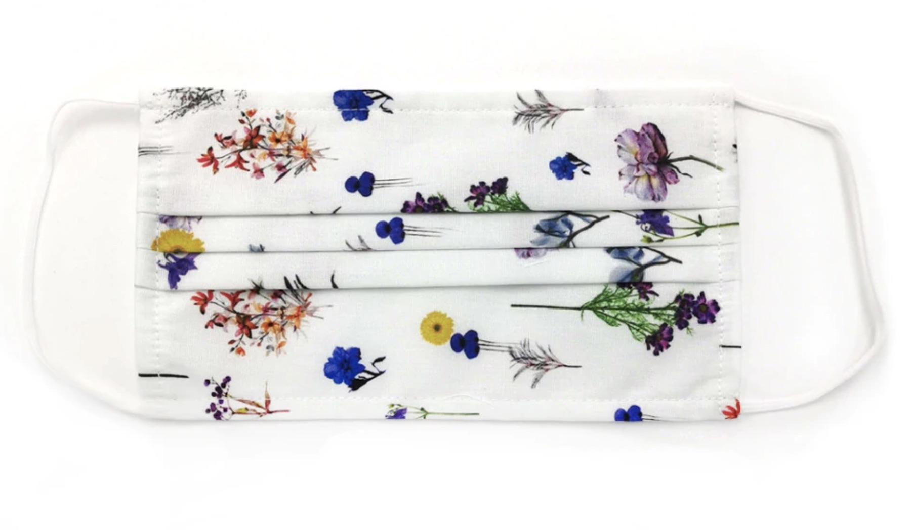 Mascarilla de tela higiénica lavable de algodón y filtro TNT con estampado floral en blanco.