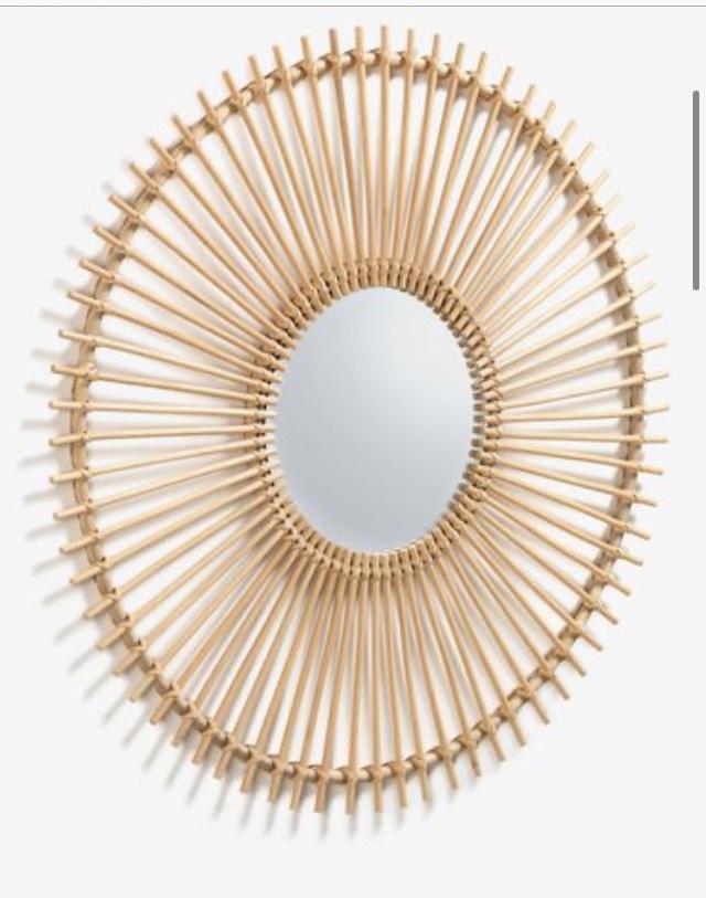 El espejo Louisa tiene un marco de ratán con un acabado natural y forma de sol