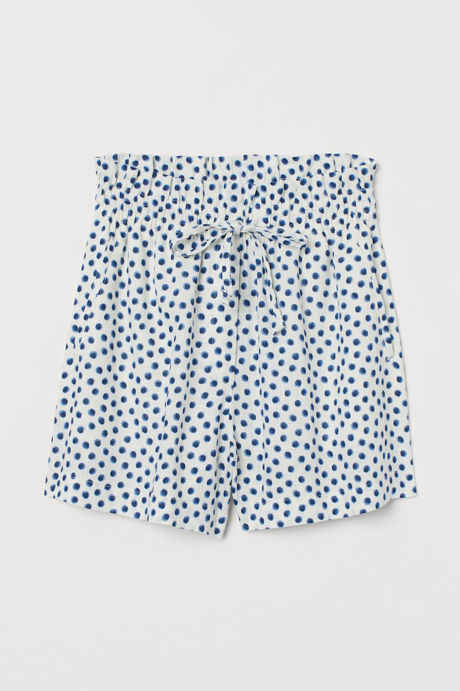 Pantalón corto en mezcla de lino y viscosa. Modelo de talle alto con cierre decorativo, cintura elástica de volantes con cordón de ajuste y bolsillos al bies.