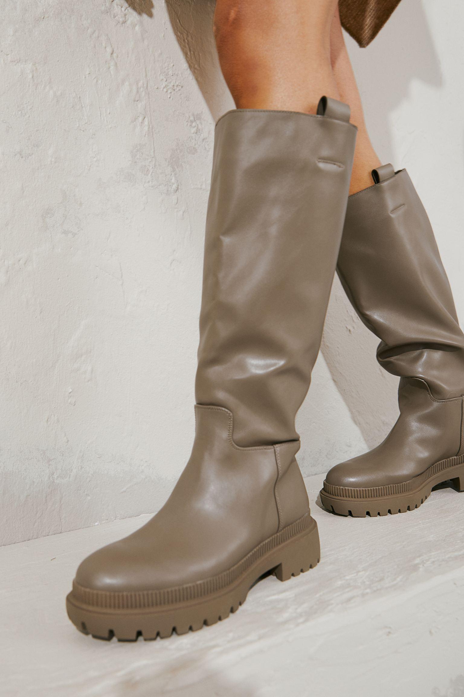 Botas a la rodilla en piel sintética con trabillas laterales. Forro de satén y plantillas en piel sintética. Suela gruesa con diseño. Tacón 5,5 cm.