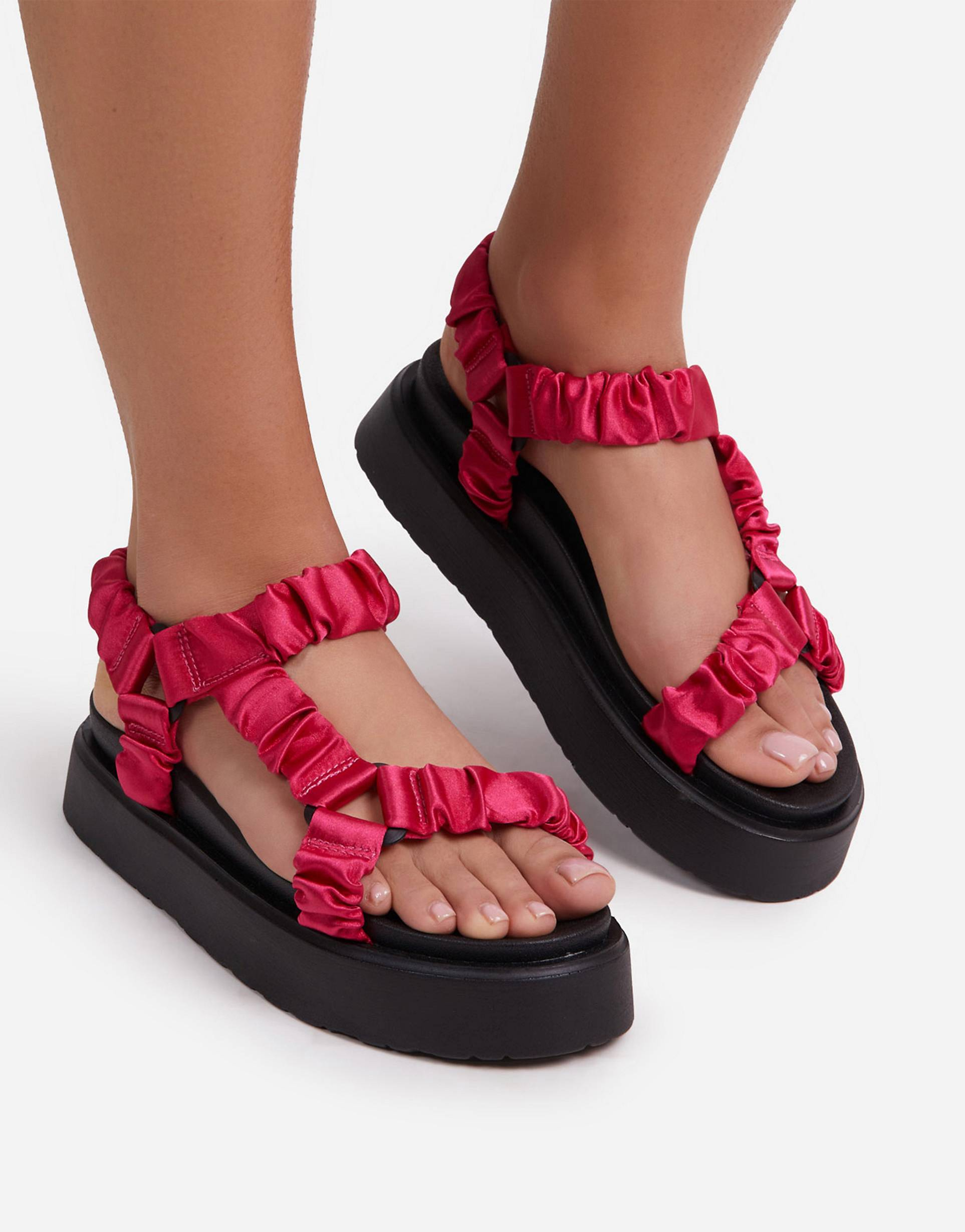 Sandalias rosas con tiras fruncidas y plataforma plana.