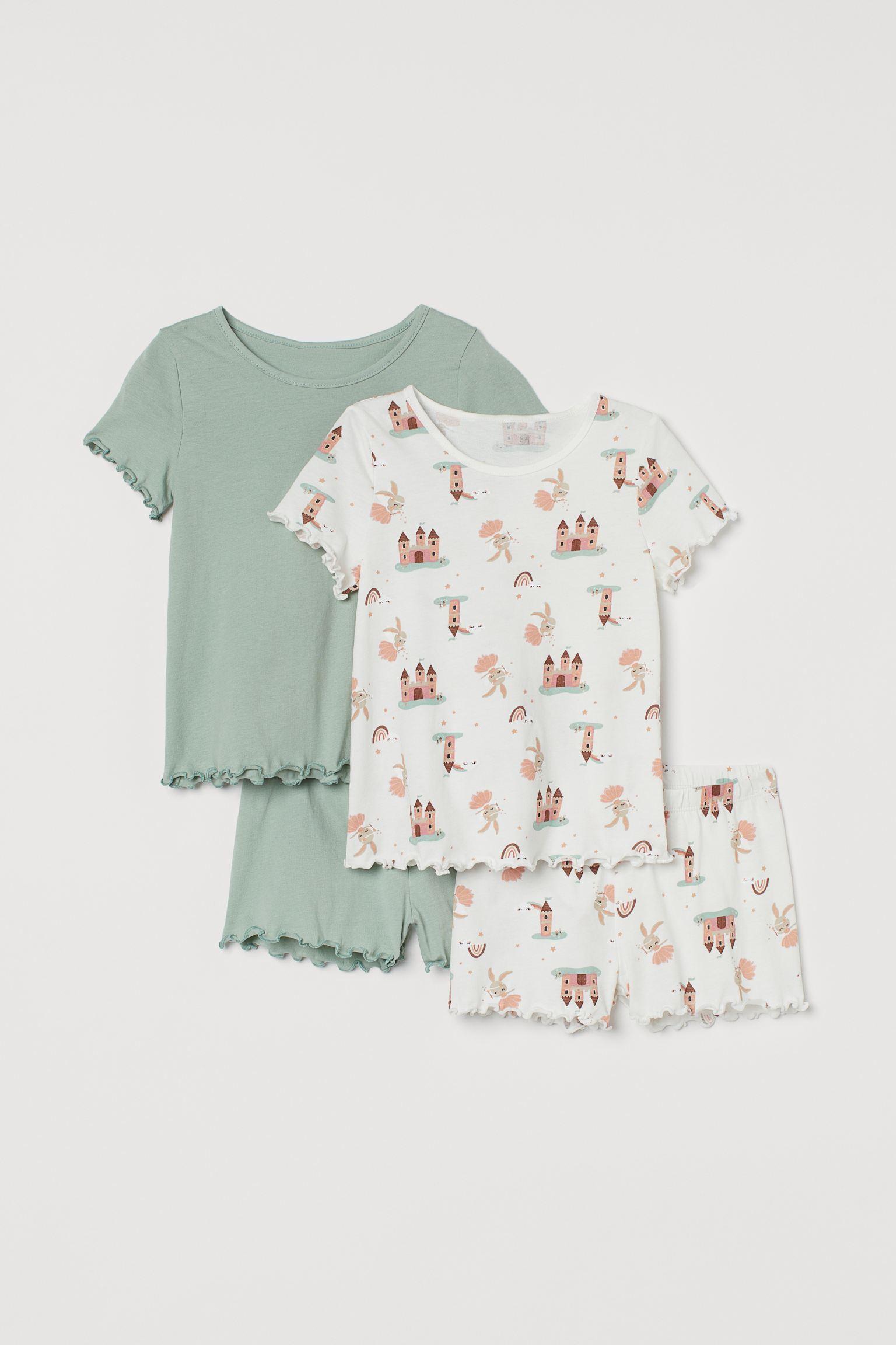 Pijamas en punto suave de algodón con ribetes sobrehilados. Camiseta con cuello fino ribeteado. Pantalón corto con cintura elástica suave.