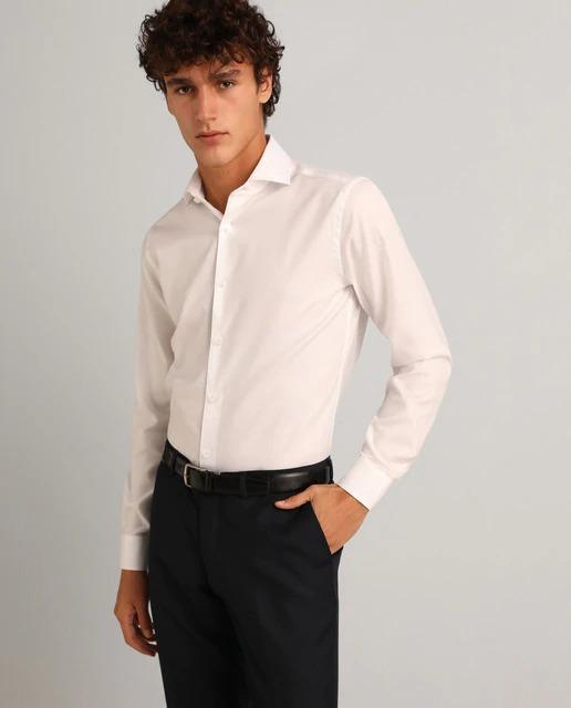 Camisa de vestir slim fit de color blanco lisa. Tiene cuello clásico y puños rectos. Fácil plancha por su acabado especial.  Slim Fit Muy entallado, sienta como una segunda piel. Sisa estrecha, ancho de manga ceñido al brazo y contorno ajustado.