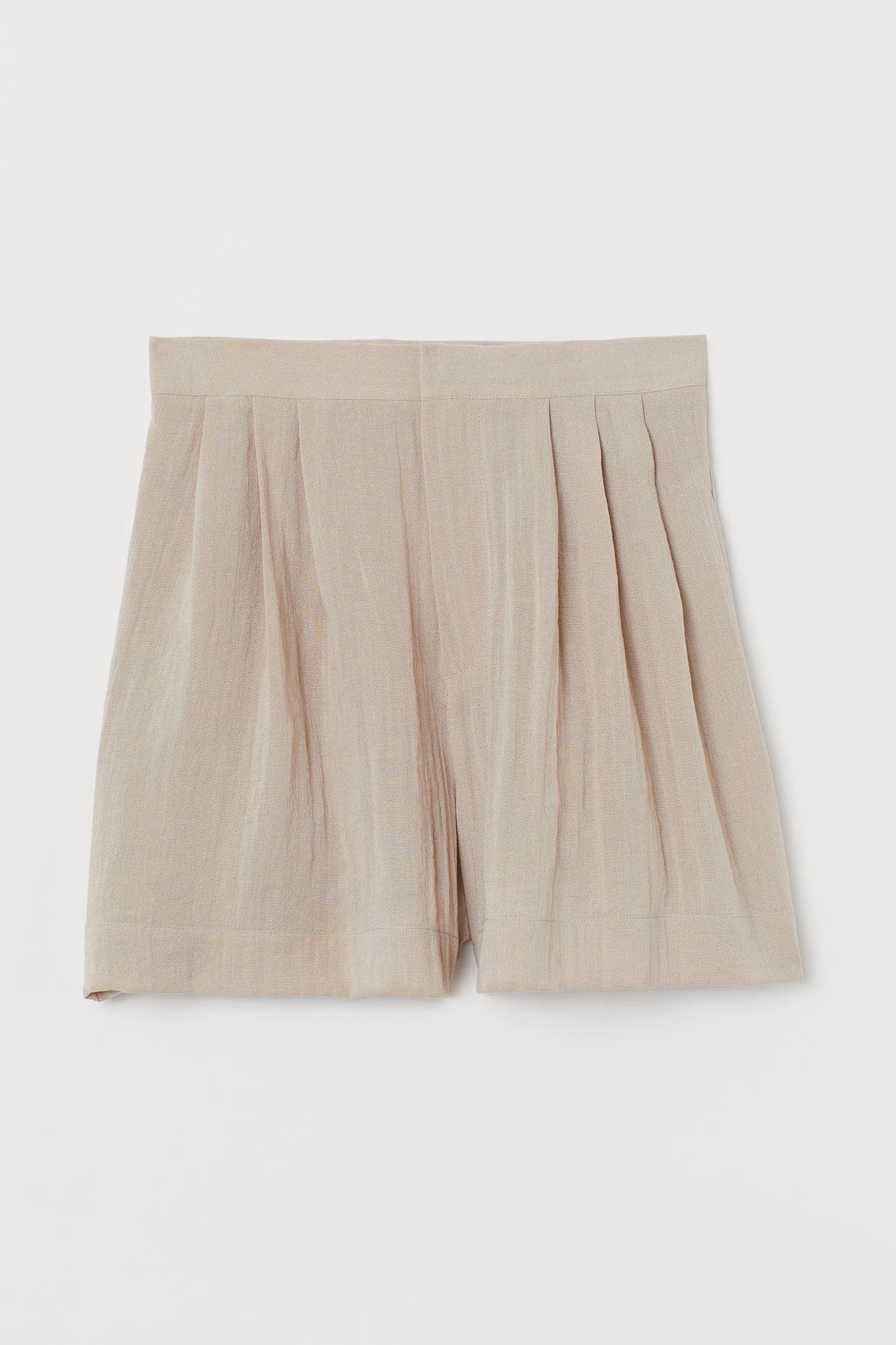 Bermuda de talle alto con pinzas, bolsillos al bies discretos y perneras amplias.