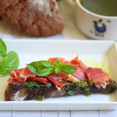 Tostas de pan de centeno con pesto y lascas de jamón, receta para un aperitivo de lujo