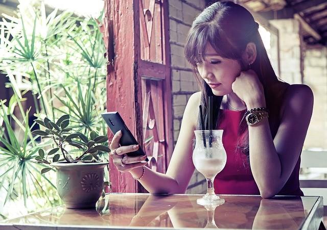Mujer asiática consultando el móvil.
