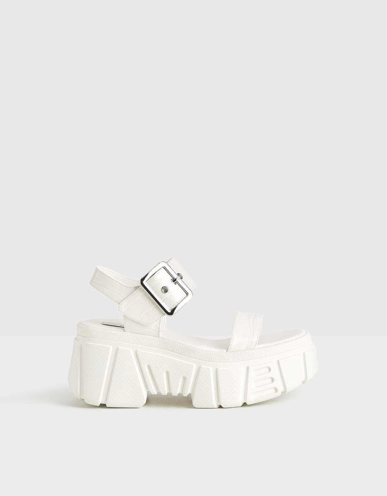 Sandalia en color blanco. Suela con volumen. Cierre mediante tira con hebilla.