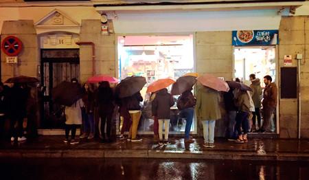 Hay gente haciendo cola bajo la lluvia en Madrid para comerse un plato de cereales