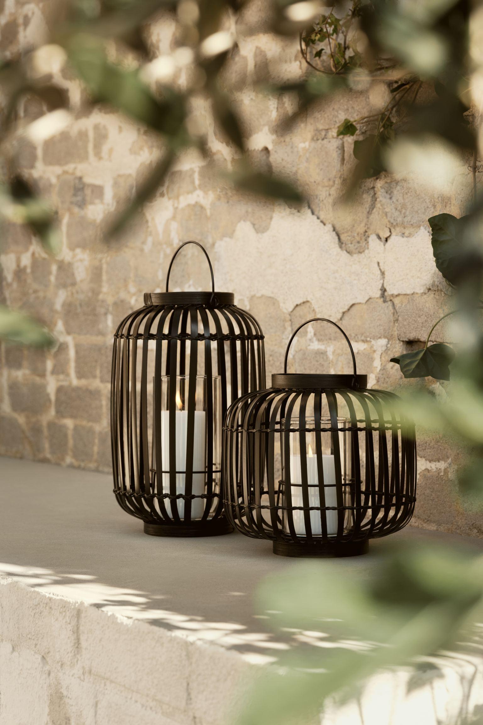 Farolillo de metal revestido en bambú con portavelas de vidrio y asa arriba. Diámetro aprox. 21,5 cm. Alto 34 cm.