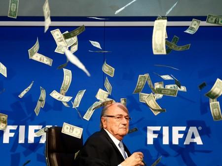 Joseph Blatter, presidente de la FIFA, bajo la lluvia de billetes que le arrojo un activista. Imagen: Business Insider.