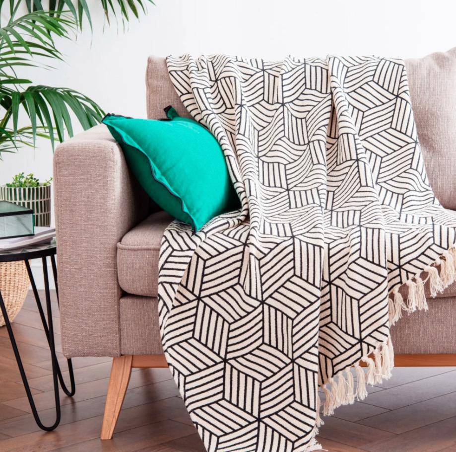 Manta de algodón color crudo con motivos decorativos gráficos negros y flecos 130x170
