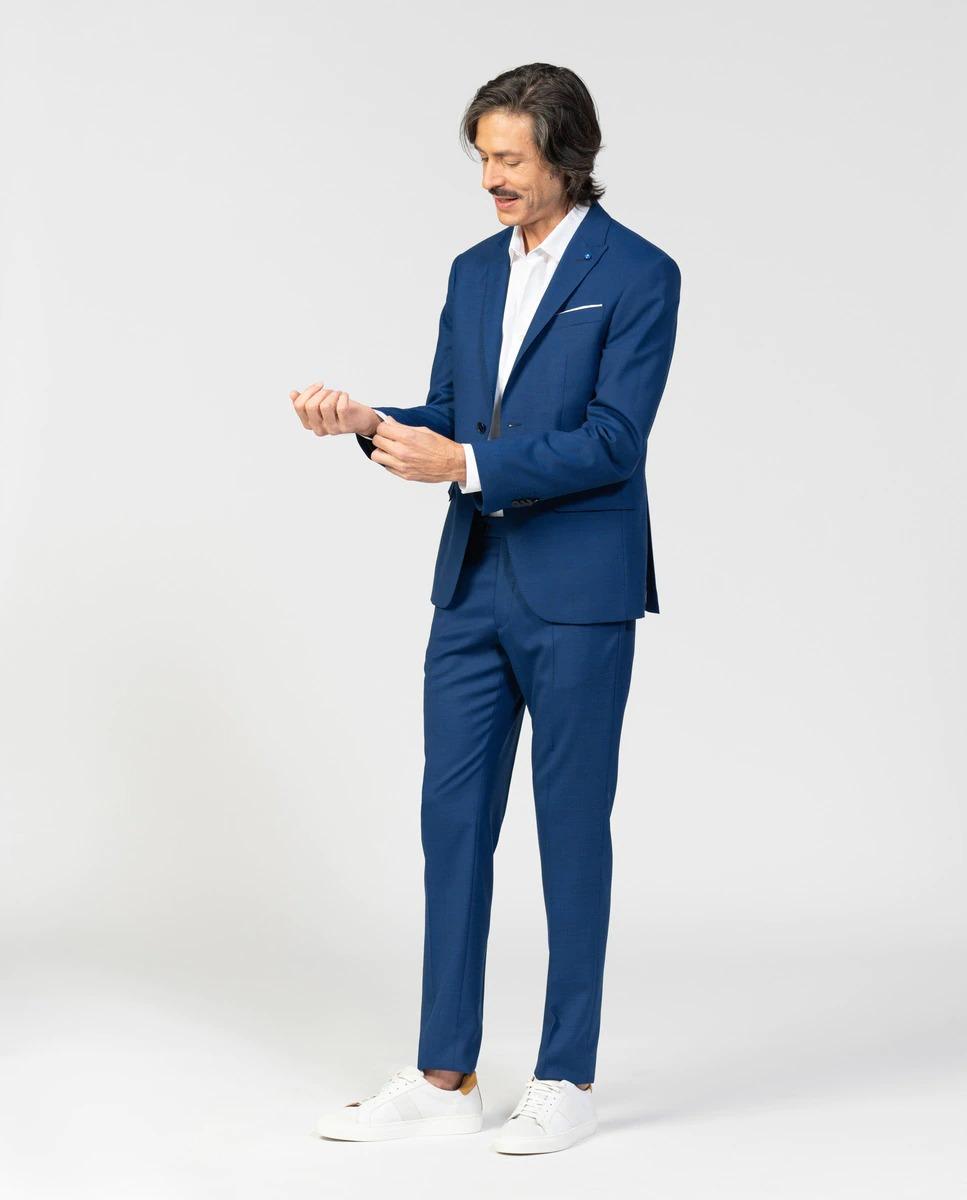 Traje Slim Fit realizado en una microestructura de lana mezcla. El elastán le proporciona confort y libertad de movimientos a la prenda. La chaqueta presenta cierre de dos botones, picadillo, dos aberturas en la espalda y punté en solapa pico y carteras bolsillos. Tiene una largo de 73 cm para la talla 50.