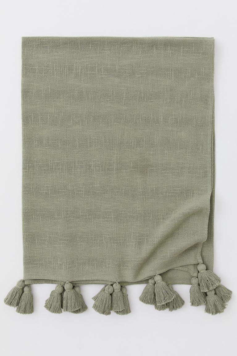Manta de algodón reciclado con poliéster reciclado en la trama. Flecos decorativos maxi en los lados cortos