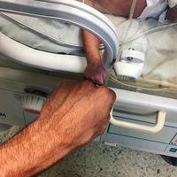 La emotiva imagen de un bebé prematuro y su médico, que transmite en un sencillo gesto la complicidad y lucha por la vida