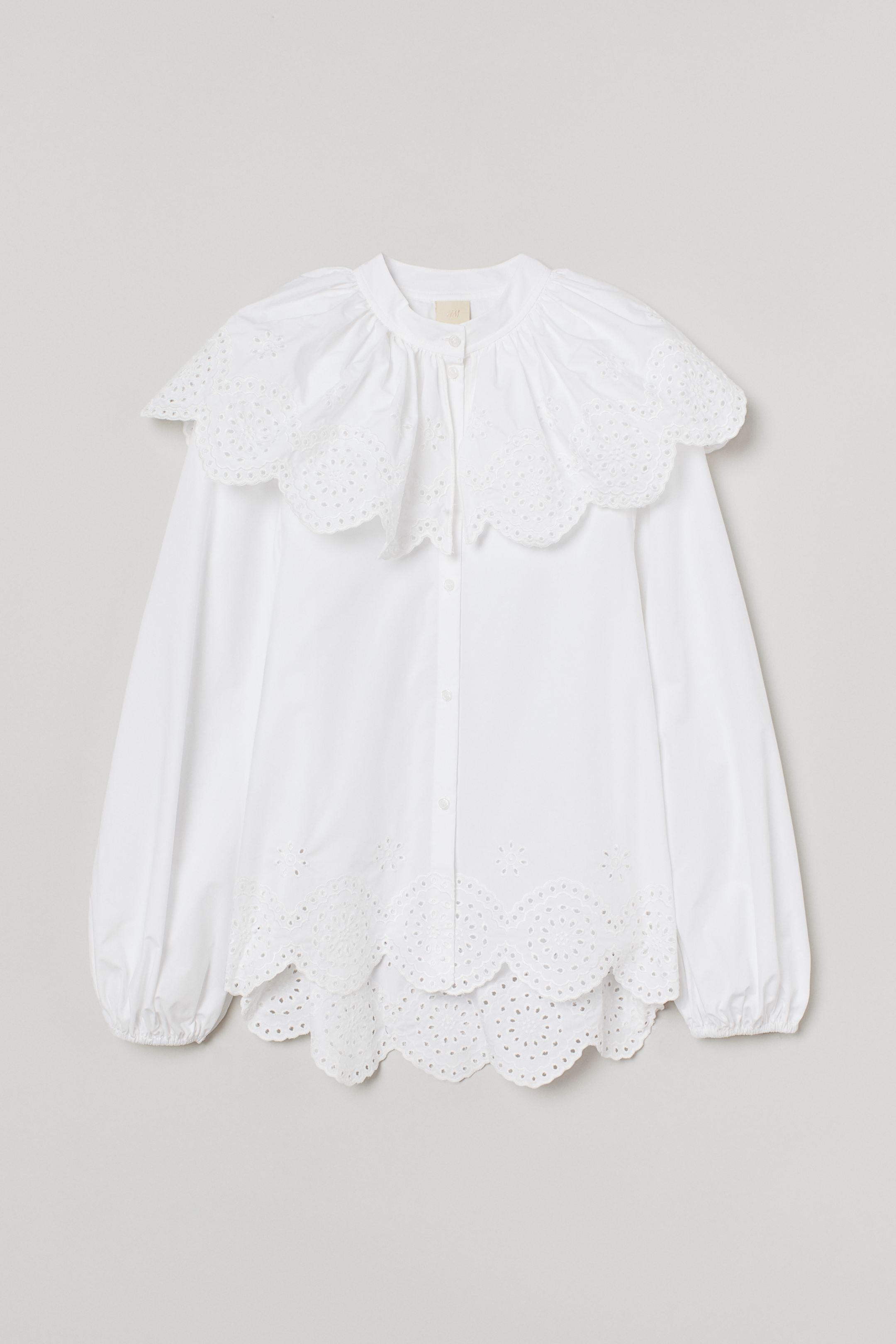Blusa amplia de algodón con bordado inglés, cuello elevado corto con capa semisuelta que cubre los hombros. Botones delante, mangas globo largas con elástico fino revestido en los puños y bajo festoneado.