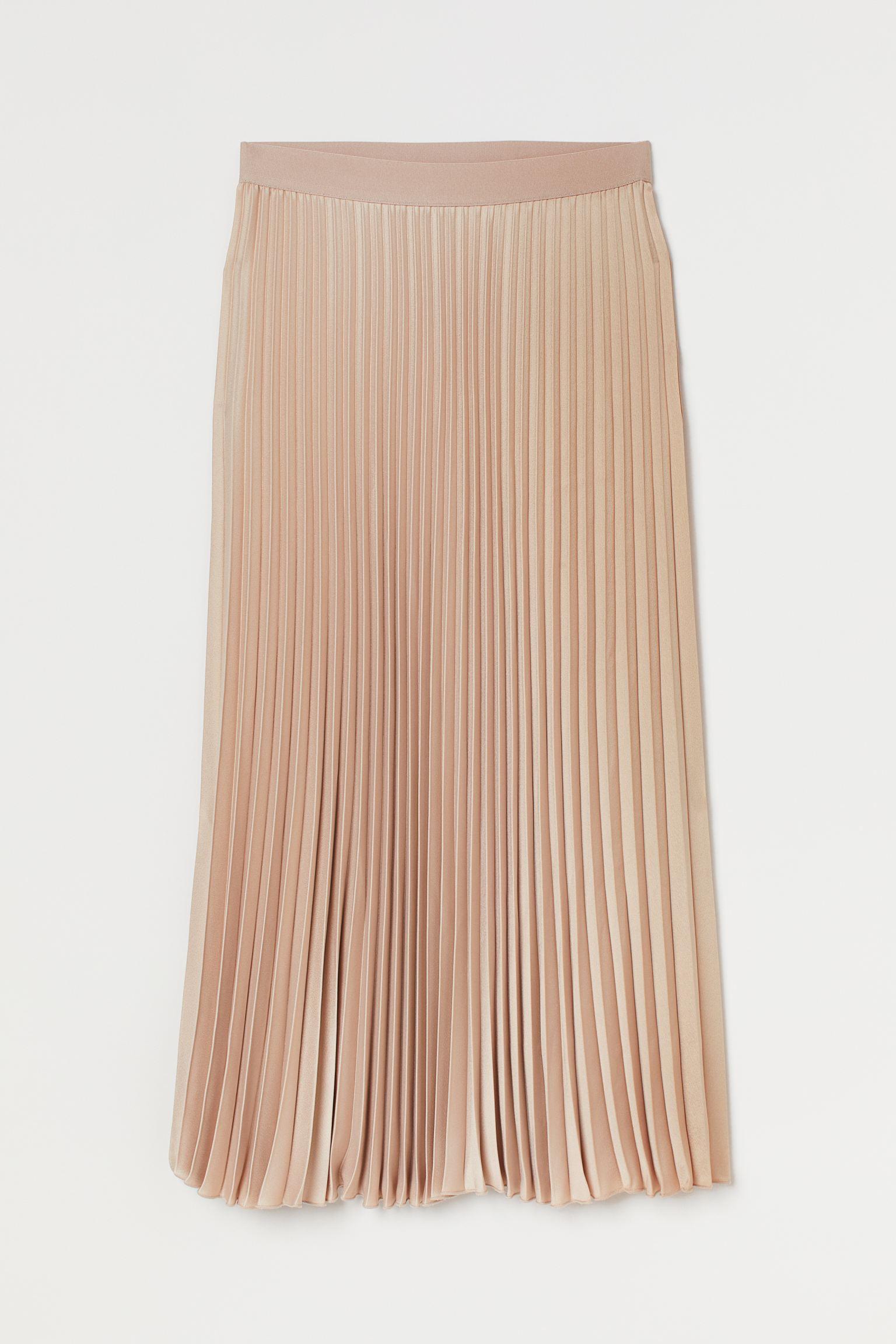 Falda midi plisada con ligero brillo. Modelo de talle alto con cintura elástica y bajo sobrehilado.