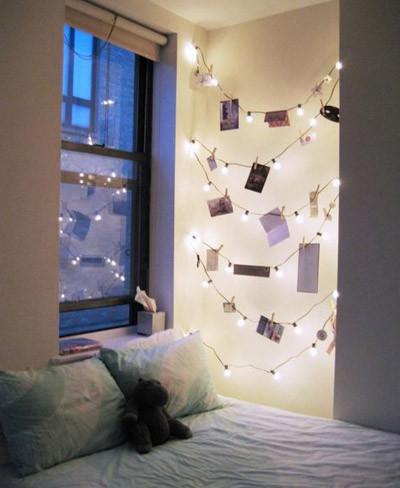 Una buena idea: combina una guirnalda de luces con fotografías para decorar un rincón del dormitorio
