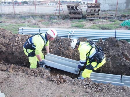 Dos trabajadores de Telice utilizan exoesqueletos para levantar objetos pesados.