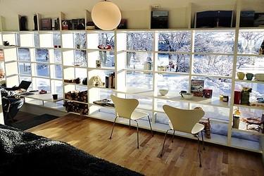 Una estantería modular acoplada a un gran ventanal, una idea luminosa