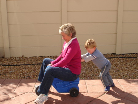 Child Pushing Grandmother On Plastic Tricycle