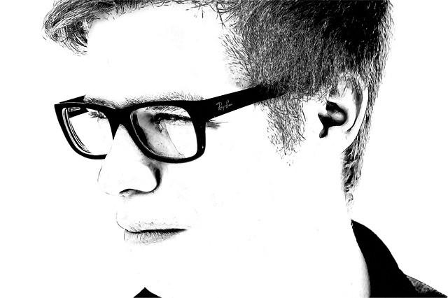 Chico joven con gafas(lentes) mira a la izquierda.Blanco y negro.