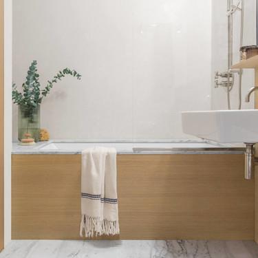 Mármol y madera en la reforma de este baño, que da como resultado un baño de diseño atemporal
