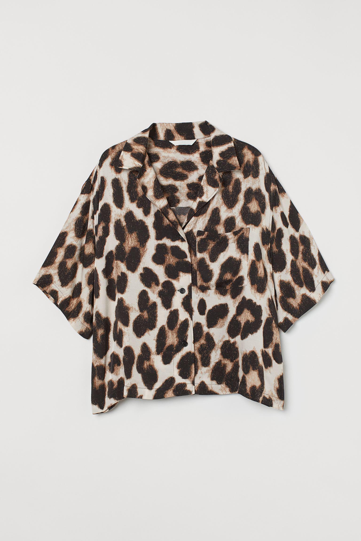 Camisa amplia en tejido de viscosa con ligero brillo y suave caída. Modelo con cuello abierto, escote de pico, botones delante y canesú en la espalda. Bolsillo superior, hombros caídos y media manga.