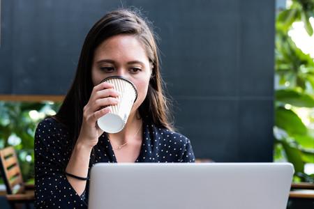 mujer ante ordenador bebiendo café