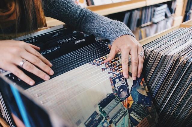 Manos buscan discos de vinilo en una tienda.