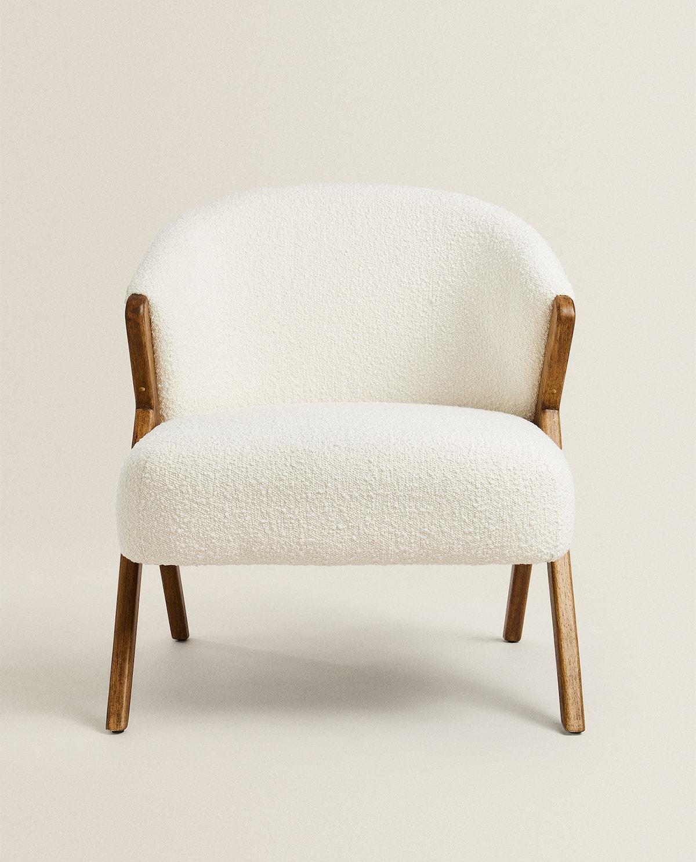Butaca tapizada con tejido bouclé con laterales y patas de madera a contraste