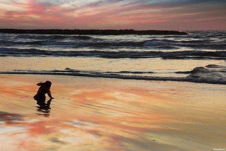 """Jugando en la playa: tira las piedras """"plop-plop"""""""