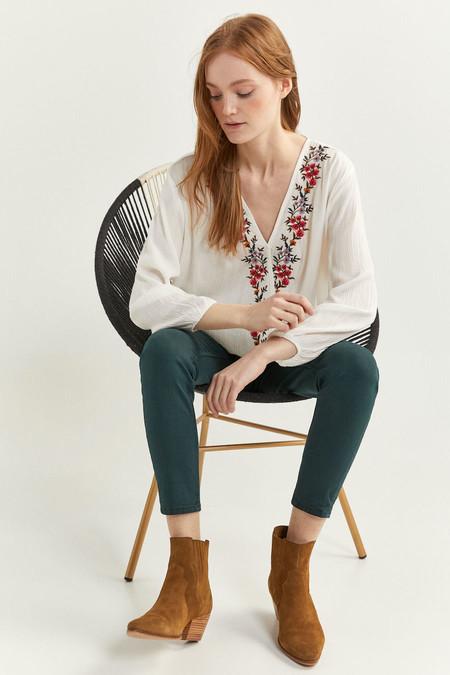 Blusa de manga larga, con cuello cruzado y detalle de bordado de flores.