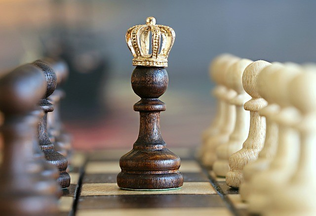 Peón de ajedrez con corona de rey.