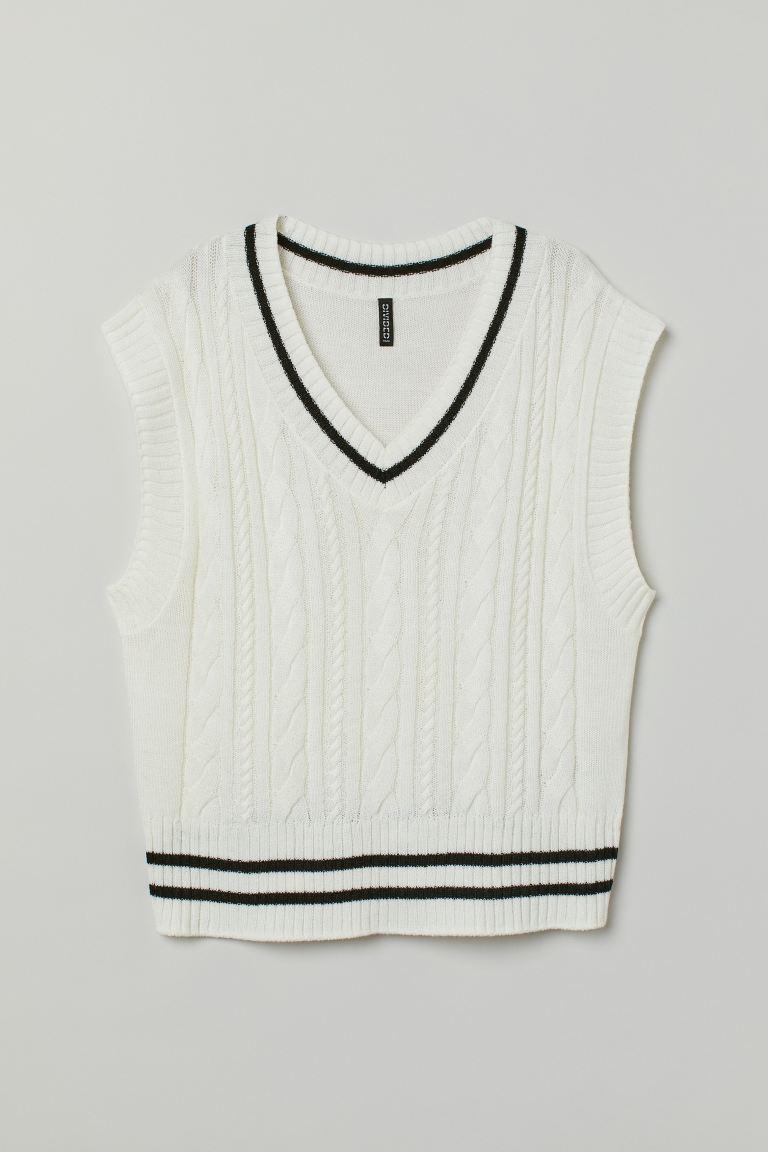 Suéter sin mangas en punto trenzado suave. Modelo con escote de pico y ribete de canalé con rayas a contraste en cuello y bajo.