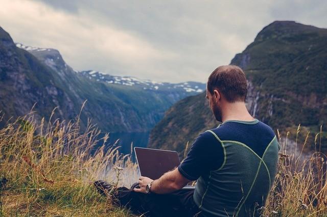 Hombre de espaldas en la montaña, sentado con un portátil.