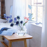 Jarrones de vidrio con flores frescas, complementos ideales para una mesa de verano