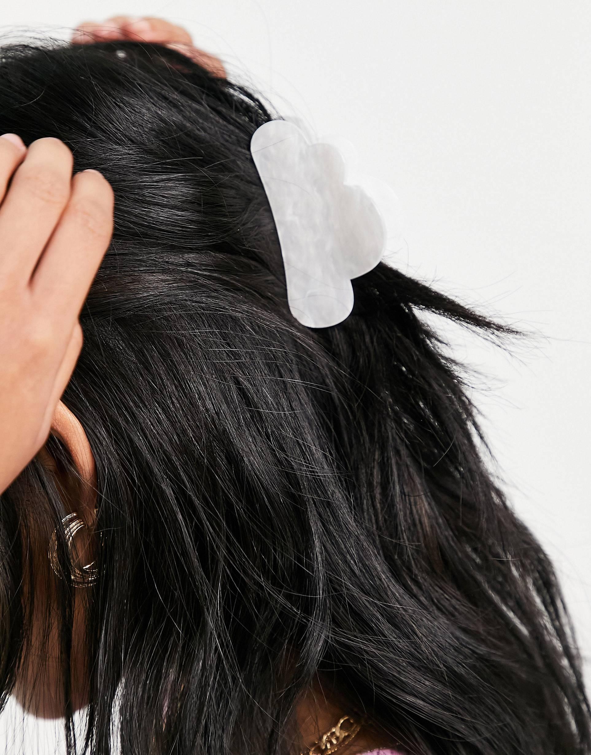 Pinza para el cabello blanca con acabado perlado.