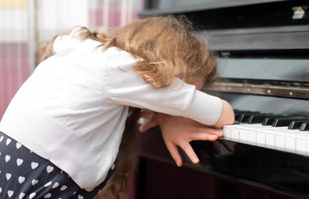 niña cansada de tocar el piano